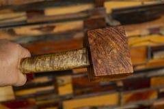 Mano del hombre que sostiene un martillo del mazo hecho de las herramientas de madera del burl para utilizado por el carpintero e foto de archivo libre de regalías