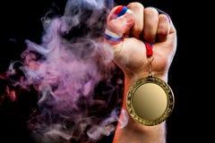 Mano del hombre que sostiene una medalla de oro imagen de archivo libre de regalías