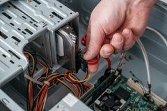 Mano del hombre que tapa el serial de SATA EN el accesorio, cable de datos de Serial ATA en dispositivo del disco duro fotografía de archivo libre de regalías
