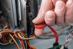 Mano del hombre que tapa el serial de SATA EN el accesorio, cable de datos de Serial ATA en dispositivo del disco duro Interfaz d fotos de archivo