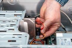 Mano del hombre que tapa el serial de SATA EN el accesorio, cable de datos de Serial ATA en dispositivo del disco duro Interfaz d imagenes de archivo