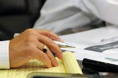 Mano del hombre que toma notas en la reunión de la construcción imagen de archivo