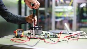 Mano del hombre del técnico usando la punta de prueba del destornillador y del multímetro digital para comprobar y para medir el  almacen de metraje de vídeo