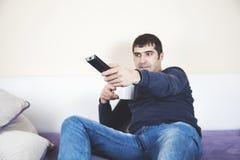 Mano del hombre teledirigida en el sofá foto de archivo