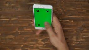 Mano del hombre usando smartphone con la pantalla verde almacen de video