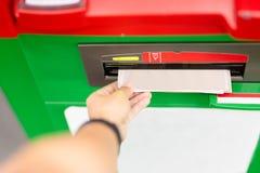 Mano del hombre usando una máquina del cajero automático con la tarjeta de crédito fotos de archivo libres de regalías