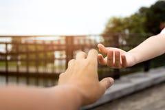 Mano del hombre y de la mujer que alcanza el uno al otro imagen de archivo libre de regalías