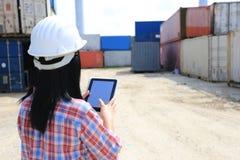 Mano del ingeniero que sostiene la tableta digital con la pantalla en blanco en fondo delantero del envase y de las importaciones imagen de archivo