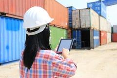 Mano del ingeniero que sostiene la tableta digital con la pantalla en blanco en fondo delantero del envase y de las importaciones fotografía de archivo