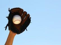Mano del jugador de béisbol con el guante y de la bola sobre el cielo Imagen de archivo libre de regalías