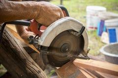 Mano del lavoratore e mobilia di legno di taglio elettrico della sega, fotografie stock libere da diritti