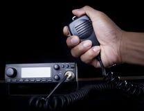 Mano del locutor y de la prensa que se sostienen de radio aficionados imagenes de archivo