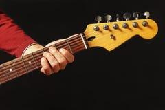 Mano del músico detrás del cuello de la guitarra eléctrica en fondo negro Fotos de archivo libres de regalías