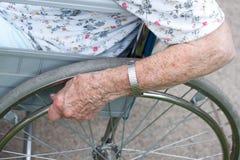 Mano del mayor en la rueda del sillón de ruedas Foto de archivo