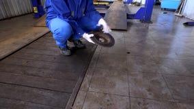 Mano del mecánico que muestra el disco de freno oxidado llevado en el garaje almacen de video