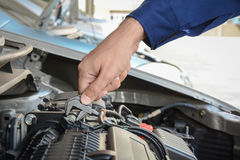 Mano del meccanico con il motore di automobile della riparazione della chiave Fotografie Stock