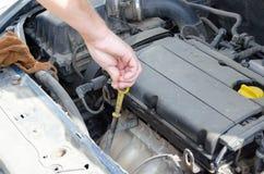 Mano del meccanico con uno strumento sotto il cappuccio dell'automobile fotografie stock libere da diritti
