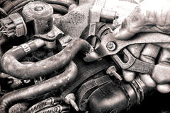 Mano del mecánico de la reparación auto que fija una pieza del motor de coche Fotografía de archivo