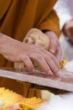 Mano del monje budista que pinta símbolos religiosos Imágenes de archivo libres de regalías
