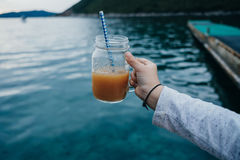 Mano del muchacho con el zumo de naranja de la vitamina en un tarro de cristal en el backgro Fotos de archivo libres de regalías