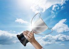 mano del negocio con el cielo azul y las llamaradas del trofeo Fotos de archivo