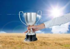 mano del negocio con el trofeo en un campo con el cielo azul Fotos de archivo