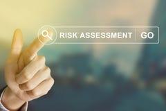 Mano del negocio que hace clic el botón de la evaluación de riesgos en barra de herramientas de la búsqueda imágenes de archivo libres de regalías
