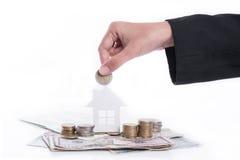 Mano del negocio que lleva a cabo el domicilio familiar del anuncio de la moneda del dinero Imagen de archivo