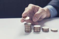 Mano del negocio que pone negocio cada vez mayor de la pila de la moneda del dinero imagen de archivo