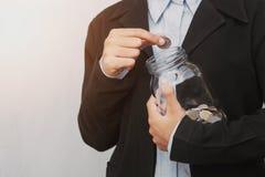 mano del negocio que pone monedas en el tarro de cristal para el accoun de ahorro del dinero imágenes de archivo libres de regalías