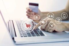 Mano del negocio que sostiene la tarjeta de crédito con el ordenador y hacer compras Fotos de archivo libres de regalías