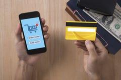 Mano del negocio que sostiene la tarjeta de crédito con el teléfono elegante y hacer compras Imagen de archivo