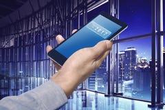Mano del negocio que sostiene un smartphone con el número 2017 en el searc Imagenes de archivo