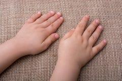 Mano del niño con el fondo de la lona Imagen de archivo