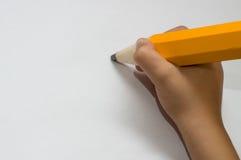 Mano del niño con el lápiz anaranjado grande Foto de archivo libre de regalías
