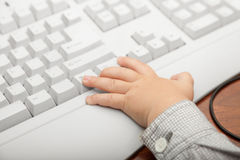 Mano del niño del niño del niño pequeño en el teclado de ordenador Fotos de archivo libres de regalías