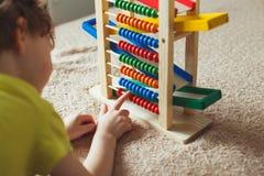 Mano del niño pequeño que juega con el ábaco Imagen ascendente de Clouse del niño lindo rizado que juega con el juguete de madera fotografía de archivo libre de regalías