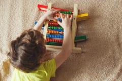 Mano del niño pequeño que juega con el ábaco Imagen ascendente de Clouse del niño lindo rizado que juega con el juguete de madera fotos de archivo libres de regalías