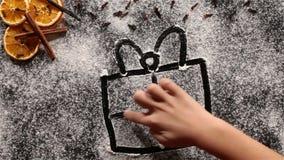 Mano del niño que dibuja el regalo de Navidad grande en harina almacen de metraje de vídeo