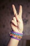 Mano del niño que muestra la muestra de la victoria con las pulseras del telar del arco iris Imagen de archivo libre de regalías