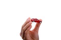 Mano del niño que sostiene un coche rojo Imagen de archivo libre de regalías