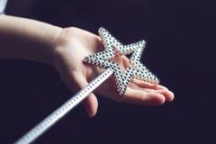 Mano del niño que sostiene una vara mágica Fotos de archivo libres de regalías