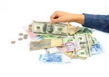 Mano del niño que escoge el billete de banco americano del dólar Fotografía de archivo libre de regalías