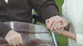 Mano del paciente en silla de ruedas, programa voluntario, concepto de la tenencia de la mujer de la caridad almacen de metraje de vídeo