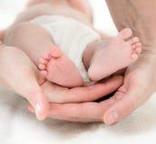 Mano del padre y pies de los bebés Imágenes de archivo libres de regalías