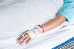 Mano del paziente femminile con IV il piercing dell'ago del gocciolamento nell'ospedale fotografie stock