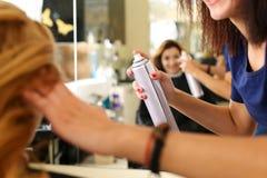 Mano del peluquero de sexo femenino que sostiene la poder de espray Imagen de archivo