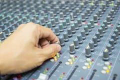 Mano del primer de la consola de mezcla del control del hombre de un sistema de alta fidelidad grande el equipo de audio fotografía de archivo libre de regalías