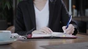 Mano del primer de una mujer que hace notas en un cuaderno Empresaria joven Sitting en cafetería en la tabla de madera almacen de video