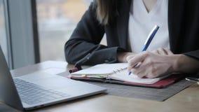 Mano del primer de una mujer que hace notas en un cuaderno Empresaria joven Sitting en cafetería en la tabla de madera En almacen de metraje de vídeo